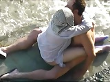 Mature husband and wife having sex on the beach.