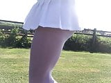 Windy upskirt in white pantyhose and pleated mini skirt