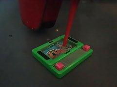 Lady L zgniata zieloną zabawkę z czerwonymi seksownymi butami.