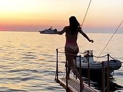 Alessandra Ambrosio jumping into the water at sunset
