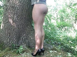Tan pantyhose and heels in the woods .