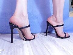 Cute feet in strappy black mules. Close up. 1080p.