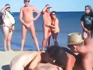 a two suck nudist women man on a beach